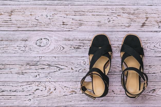 Modne czarne damskie letnie buty na drewnianym tle rustykalnym.