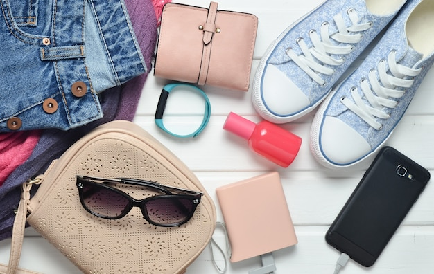 Modne damskie akcesoria, buty, ubrania i nowoczesne gadżety na białym tle drewnianych. dżinsy, torba, trampki, smartfon, inteligentna bransoletka, power bank, kosmetyki, okulary przeciwsłoneczne, szalik. widok z góry.