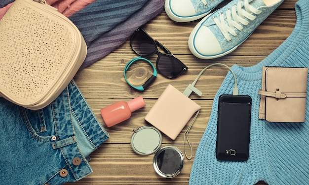 Modne damskie akcesoria, buty, ubrania i nowoczesne gadżety na drewnianym tle. dżinsy, torba, trampki, smartfon, inteligentna bransoletka, power bank, kosmetyki, okulary przeciwsłoneczne, szalik. widok z góry. leżał płasko.