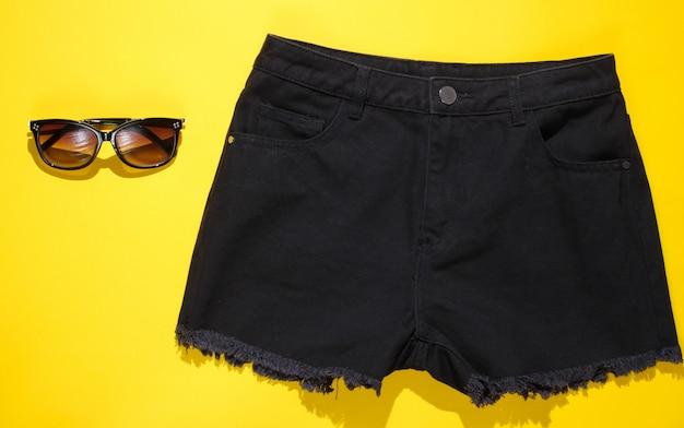 Modne damskie jeansowe czarne szorty i okulary przeciwsłoneczne. widok z góry