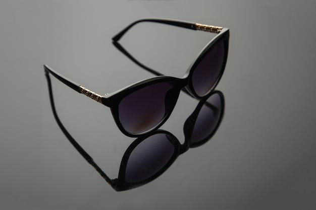 Modne damskie okulary przeciwsłoneczne, czarny plastik, złota ozdoba na natrysku, stylowe tło gradientowe z filtrem polaryzacyjnym.