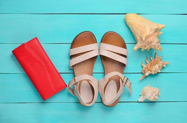 Modne damskie sandały, czerwona torebka, muszle na niebieskiej drewnianej podłodze. pojęcie podróży do morza. widok z góry.