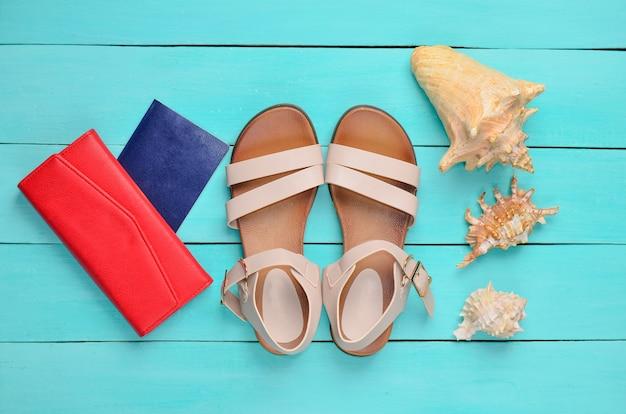 Modne damskie sandały, paszport, czerwona torebka, muszle na niebieskiej drewnianej podłodze. pojęcie podróży do morza. widok z góry.