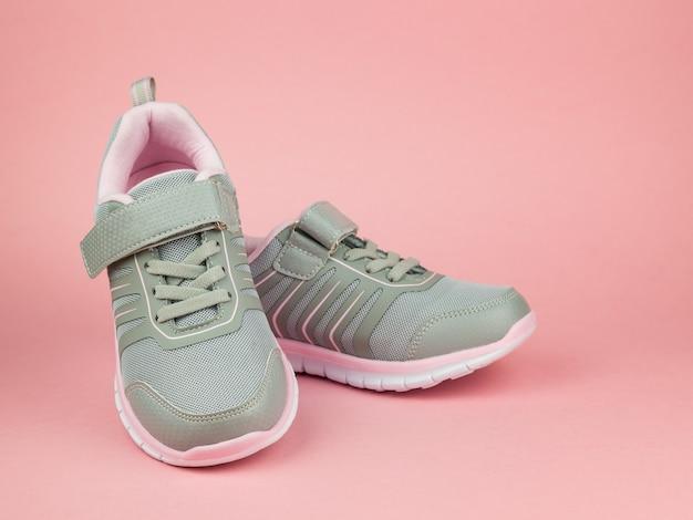 Modne damskie trampki szaro-różowe na różowym tle. buty sportowe.