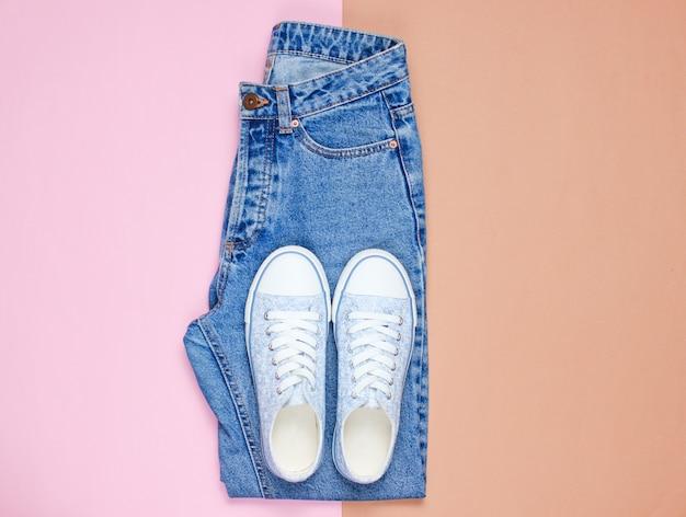 Modne damskie trampki z niebieskimi dżinsami na pastelowym tle. widok z góry, leżał płasko, minimalizm