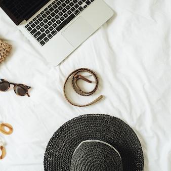 Modne dodatki damskie, okulary, kolczyki, pasek, słomkowy kapelusz, słomkowa torba i laptop leżący na łóżku z białą pościelą