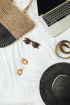 Modne dodatki damskie okulary, kolczyki, pasek, słomkowy kapelusz, słomkowa torba i laptop leżący na łóżku z białym prześcieradłem.
