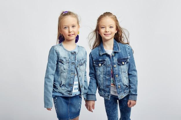 Modne dzieci pozują do wiosennej odzieży dżinsowej. radość i zabawa. spodnie jeansowe