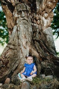 Modne dziecko w niebieskiej sukience siedzi przy starym gigantycznym drzewie i uśmiecha się
