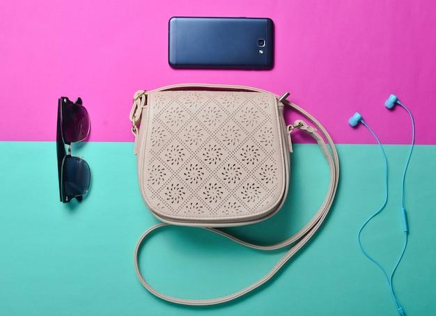 Modne dziewczęce akcesoria na wielokolorowym pastelowym tle. co jest w damskiej torbie? trend minimalizmu. skórzana torba, okulary przeciwsłoneczne, smartfon, słuchawki.