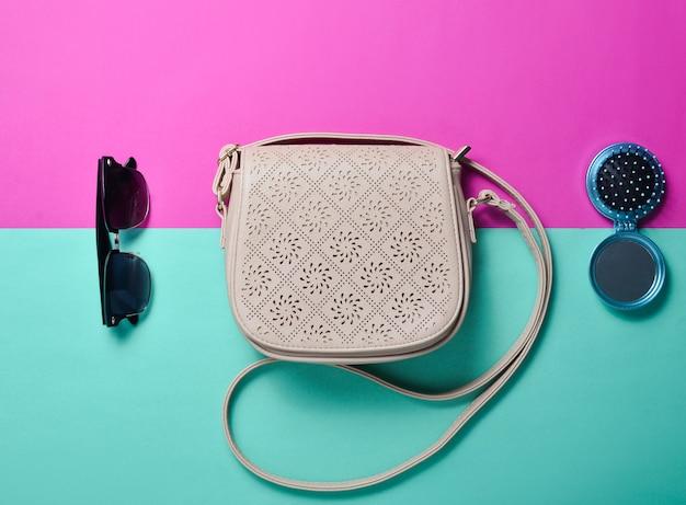 Modne dziewczęce akcesoria na wielokolorowym pastelowym tle. trend minimalizmu. skórzana torba, okulary przeciwsłoneczne, lusterko grzebieniowe.