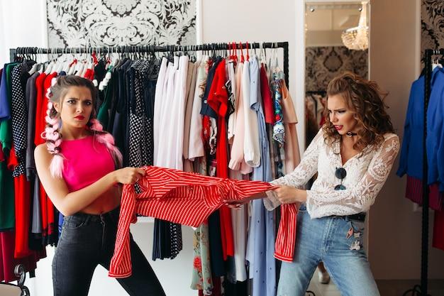 Modne dziewczyny na zakupach rozmawiają ze sobą w sklepie.