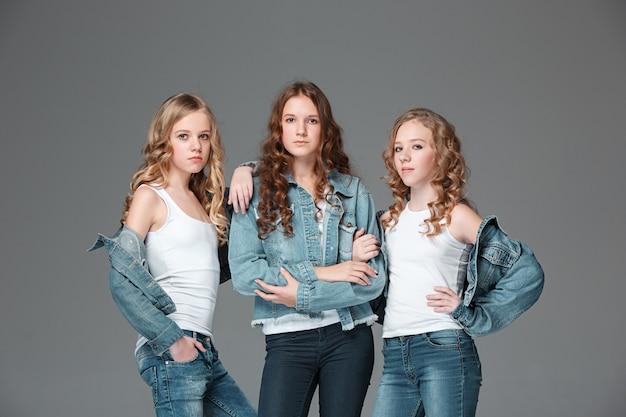 Modne dziewczyny stojące razem i na szaro