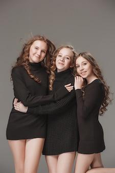 Modne dziewczyny stojące razem i patrząc na aparat na szarym