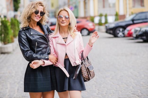 Modne dziewczyny w okularach stojących na ulicy
