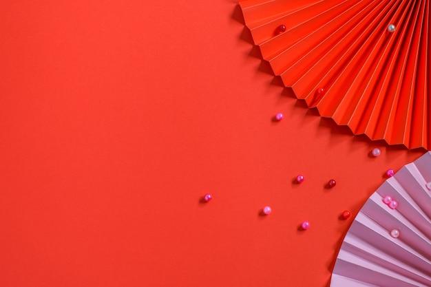 Modne ekologiczne papierowe wachlarze i fasolki na czerwonym tle. ładny design na kartkę z życzeniami, zaproszenie na imprezę lub w jakimkolwiek innym celu. widok z góry, makieta zdjęcia. koncepcja diy.