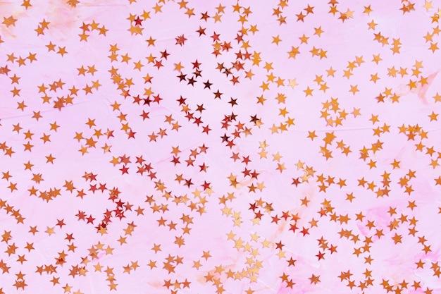 Modne gwiazdki konfetti z różowej folii na różowym tle.