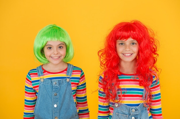 Modne i artystyczne. szczęśliwe dzieci noszą modne włosy peruki żółte tło. małe dziewczynki uśmiechają się z modnym wyglądem. modny salon fryzjerski. moda i styl.