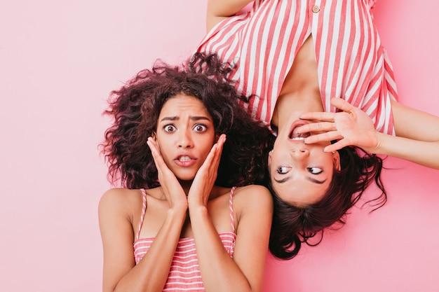 Modne i jasne dziewczyny o pięknych brązowych oczach i stylowych włosach, ubrane w sukienki w paski o delikatnym różowym kolorze