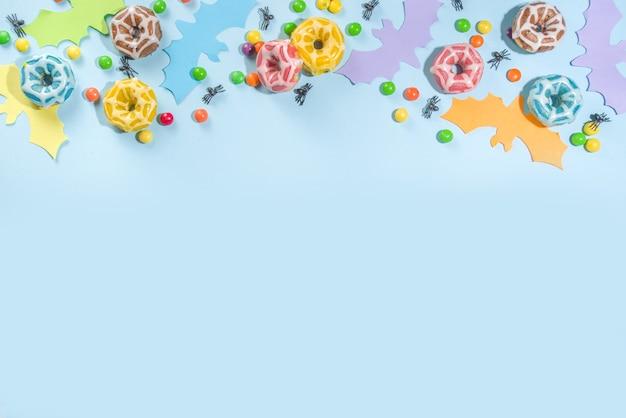 Modne jasne kolorowe tło halloween, z papierowymi symbolami halloween fioletowy, niebieski, żółty, pomarańczowy - nietoperze, duch, słodycze i cukierki. jasnoniebieskie tło, płaskie miejsce kopiowania z góry