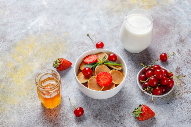 Modne jedzenie - mini pancake płatki. sterta naleśników zbożowych z jagodami i orzechami.