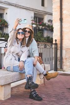 Modne koleżanki biorące selfie, siedząc na ławce na ulicy