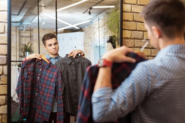 Modne koszule. spokojny, ciekawy młodzieniec wybiera modne ciuchy w sklepie i czuje się usatysfakcjonowany patrząc na dwie koszule