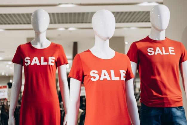 Modne manekiny w czerwonych koszulkach i wyprzedażach tekstowych stoją na wystawie sklepowej i przyciągają kupujących. czarny piątek wyprzedaż w sklepie casual.