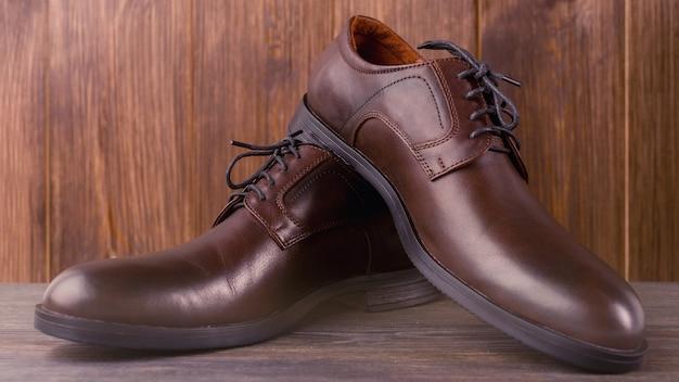Modne męskie klasyczne brązowe buty na drewnianym tle.