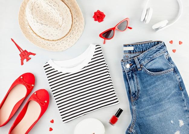 Modne mieszkanie leżało w miejskim stroju dziewczyny w stylu francuskim z koszulką, butami baleriny, okularami przeciwsłonecznymi i dżinsami.