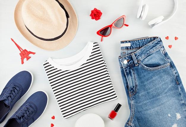 Modne mieszkanie leżało z miejskim strojem dziewczęcym w stylu francuskim z koszulką, butami baleriny, okularami przeciwsłonecznymi i dżinsami.