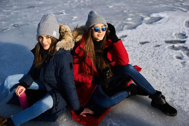 Modne młode kobiety spacerują i bawią się zimą na świeżym powietrzu