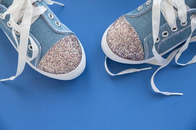 Modne niebieskie trampki dla dziewczynek na niebieskiej ścianie. para modnych dziecięcych butów sportowych. eleganckie denimowe trampki dla dzieci. para modnych błyszczących trampek z białymi sznurowadłami. styl młodzieżowy