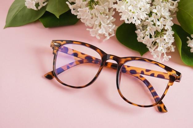 Modne okulary i gałązka białego bzu na różowym tle, okulary i kwiaty, modne oprawki okularowe