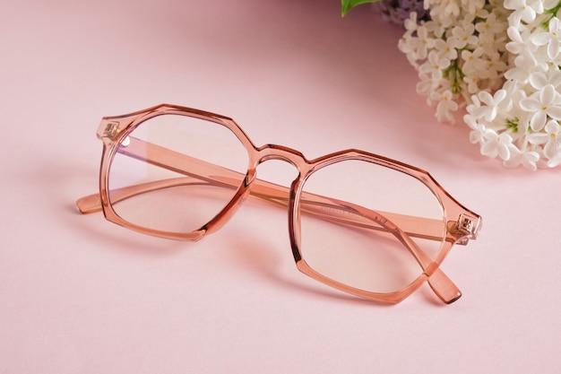 Modne okulary i gałązka białego bzu na różowym tle, okulary i kwiaty, przezroczysta kolorowa oprawka do okularów