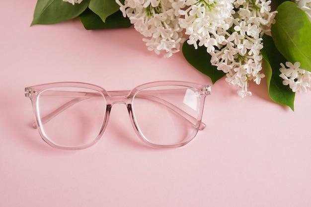 Modne okulary i gałązka białego bzu na różowym tle, okulary i kwiaty, przezroczysta oprawka na okulary