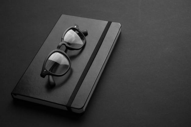 Modne okulary na czarnym zeszycie i prostym tle