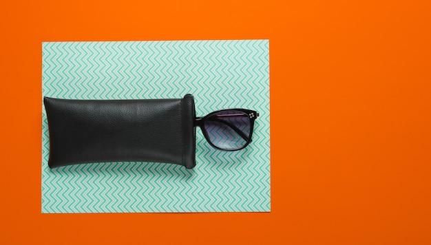 Modne okulary przeciwsłoneczne w ochronnym etui na tekturowym tle. widok z góry