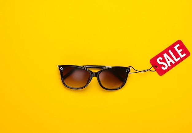 Modne okulary przeciwsłoneczne z czerwoną metką sprzedażową na żółtym tle. rabat. minimalizm