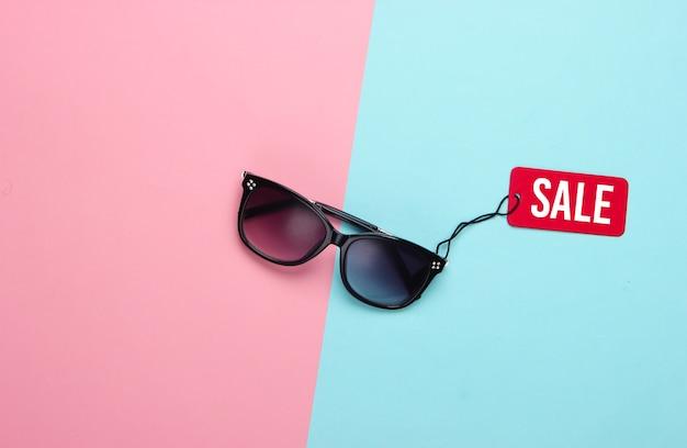 Modne okulary przeciwsłoneczne z czerwoną metką wyprzedaży na różowo-niebieskim pastelu.