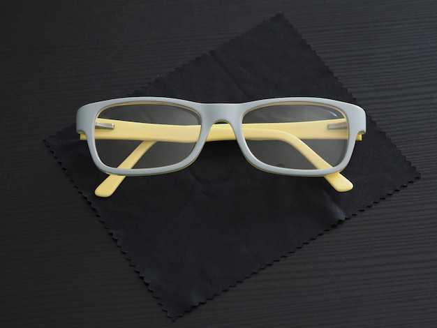 Modne okulary w żółto-szarej plastikowej oprawce leżącej na ściereczce do okularów z mikrofibry.