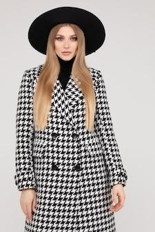 Modne piękne modelki w kapeluszu w stylowe pozowanie na białym tle na tle białego studia średni długi strzał. urocza młoda blond kobieta stojąca w eleganckich jesiennych ubraniach