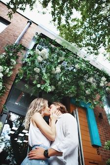 Modne piękne para całuje na zewnątrz w pobliżu domu. naturalny kolor. młody stylowy mężczyzna i kobieta przytulić w mieście w kwiatach. portret z bliska