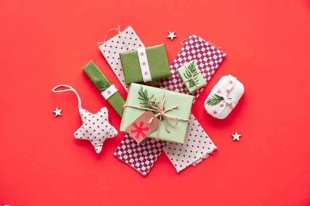 Modne, przyjazne dla środowiska ozdoby świąteczne i noworoczne bez odpadów oraz pakowane prezenty. leżał płasko, widok z góry na czerwonym papierze.