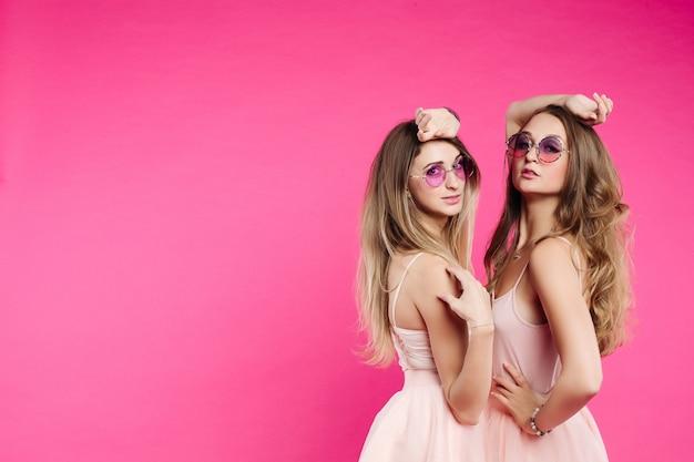 Modne siostry w różowych sukienkach i fioletowych okularach przeciwsłonecznych.