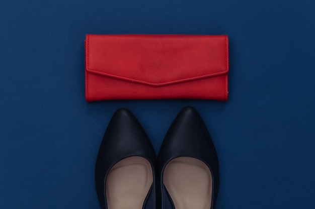 Modne skórzane buty na obcasie i portfel na klasycznym niebieskim tle. kolor 2020. widok z góry.