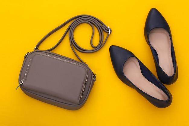 Modne skórzane buty na wysokim obcasie i torba na żółtym tle. kolor 2020. widok z góry.