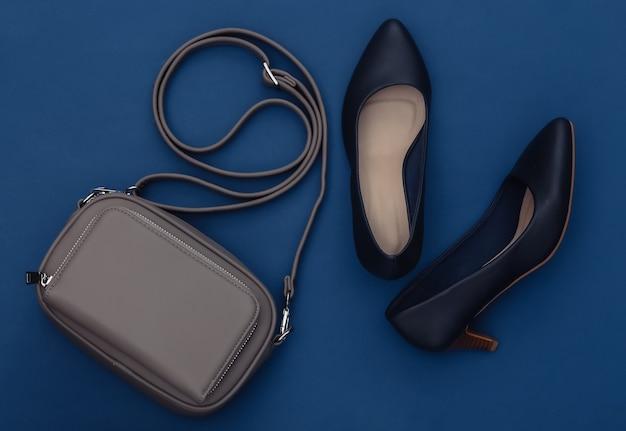 Modne skórzane buty na wysokim obcasie i torebka na klasycznym niebieskim tle. kolor 2020. widok z góry.