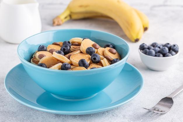 Modne śniadanie z mini naleśnikami, jagodami i kawałkami czekolady, selektywne focus.