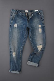 Modne spodnie jeansowe na szarym tle, widok z góry
